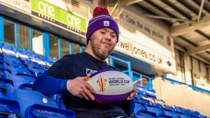 Oliver Thomason holding a Rugby League World Cup ball sat in the Halliwell jones stadium